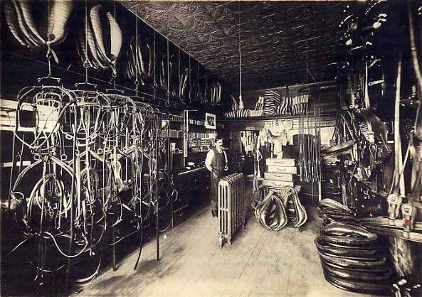 Year: 1911 Place Name: Saskatoon The picture shows my father, John Allwood in his harness shop at 830 Broadway Ave, which would be typical of the times. He returned to England for Christmas 1912 when business was flourishing and I assume this picture was taken before he left.