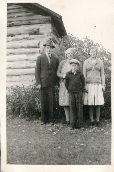 Harold, Annie, Tom & Nancy:Here we see a picture of Annie Maude with Harold, Nancy and Thomas beside their log house. This would have been taken by Robert in the fall of 1939 before Harold joined up. Maude was teaching in the Spruce Bluff School at the time.