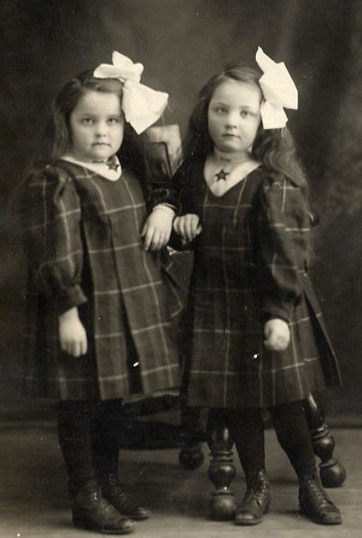 Lila & Lula Croll Year: 1910 Place Name: Brandon, MB An accomplished seamstress, Edith Croll made all of her children's clothes. These dresses were made of dark green plaid wool. The girls' hair was usually worn in braids. For special occasions they were allowed to wear it loose, (which they liked), with HUGE white taffeta bows, (which they didn't like)!