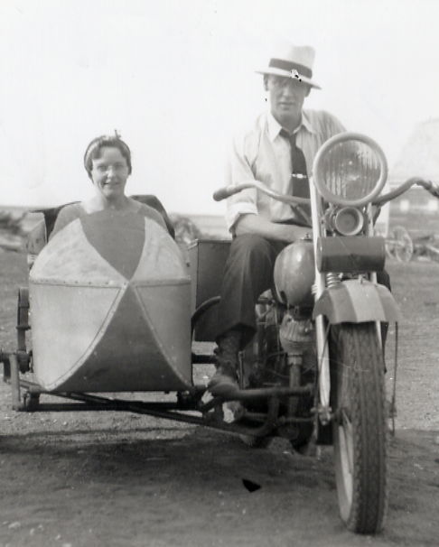 "Lila Croll & Clayton Franklin Year: mid 1930's Place Name: Croll farmyard, Richlea, SK In the years of the Depression many people could not afford a car. When he started ""keeping company with Lila Cross, Clayton Franklin solved the transportation problem by getting a sidecar for his motorcycle. Most of their travelling was on the dirt roads around Eston, Sask. In later years, Lila reminisced about two longer trips on gravel highways...to Regina, in a dust storm, and to Calgary, in a downpour."