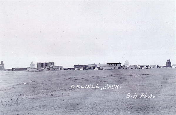 New Townsite - Delisle, Saskatchewan, November 1, 1908 Year: 1908 Place Name: Delisle August 1, 1908 - Delisle's old townsite had a store, post office, hall, livery barn and St. Ann's Catholic Church. These buildings were all moved in the fall of 1908, 3 miles north to the new townsite and by November 1, 1908 it grew to the size in this picture. Note the 4 elevators.