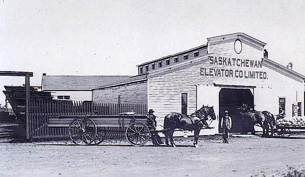 Saskatchewan Elevator Co. Limited Year: 1910 Place Name: Delisle Shown in the picture standing is Manager, Jim Thompson and standing beside his dray pulled by a team of horses is Drayman J. Draper.