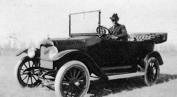 Jack Harrington in Maxwell car Year: 1917 Jack Harrington in his prized Maxwell car. Note the trees, planted in 1912.