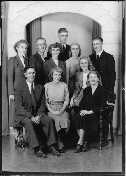 Studio portrait of Newman family in 1945 Year: 1945 The Newman family in 1945. Front row, left to right: Percy, Daphne, Gertrude. Back row, l-r: Judith, Jack, Joan, Ken, Doris, Shirley, Bernard.