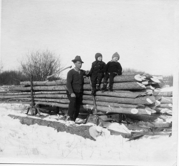 Percy with two oldest children pose with logs. Year: 1925 Percy cut firewood with Ken and Bernie to keep him company in 1925.