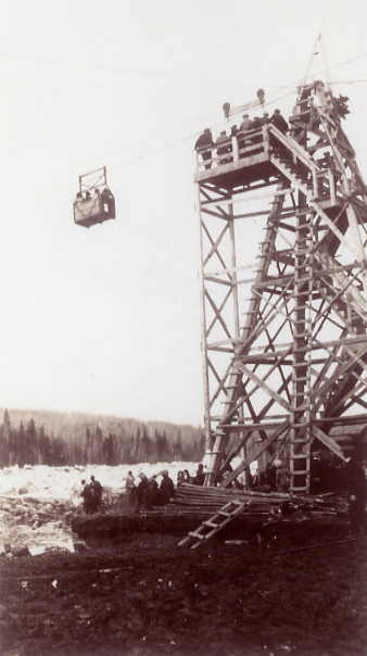 Crossing the Saskatchewan River via the Basket Year: 1928 Place Name: Nipawin The basket permitted crossings in the fall and spring when neither ferry nor ice crossing were safe. The basket hung from a cable which was pulled back and forth with a Model T Ford engine.