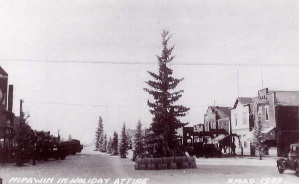 Nipawin in Holiday Attire Year: 1939 Place Name: Nipawin - 1st Ave. Image Source: unknown - taken from a postcard Spruce trees, ice blocks and coloured lights adorn Nipawin's streets during the Christmas season.