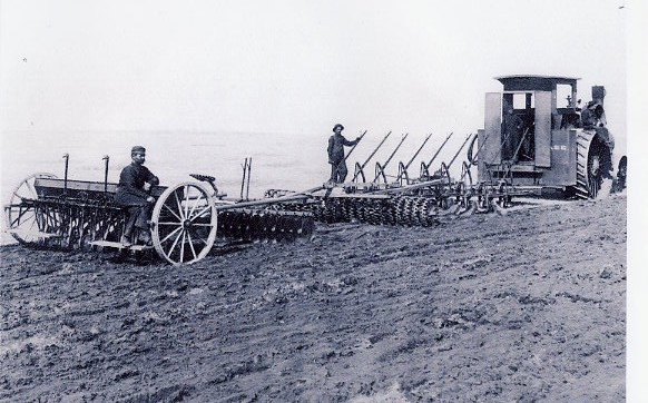 Preparing the Soil Year: circa 1910 Tractor , plough, packer, disc and seed drill breaking virgin prairie, preparing the soil and seeding a cereal crop of either wheat, oats or barley, all in one operation. Robert Owen Ross seated on the seed drill. This would be in the early years 1906 - 1910.