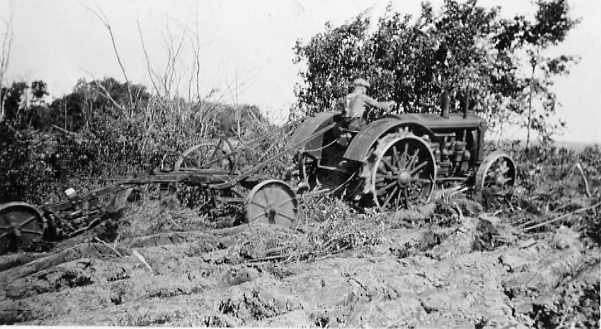 Breaking Brush  Year: 1929    Place Name: Strasburg    Image Source: H. Schwandt    W. L. Schwandt on a John Deere tractor pulling a one-way disc to prepare the bush land for seeding. The trees have previously been cut down, piled and burned.