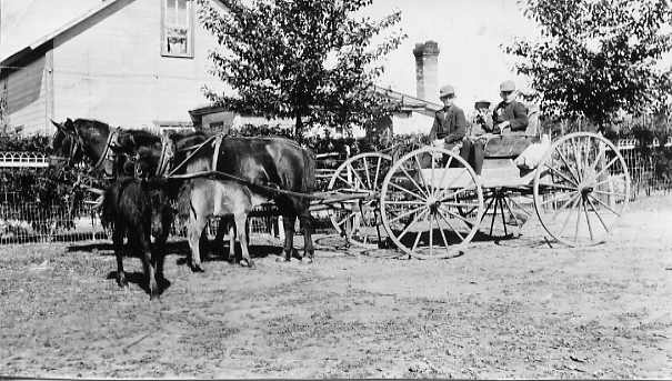 Off to school by buggy and ponies  Year: circa 1928  Place Name: Strasburg  The shetland colts nuzzle their mothers. Peggy and Jean who are harnessed and ready to take the twins Ted and Fred to school. Young Hal has climbed aboard for the picture. In winter a sleigh and team was used and horses were stabled on the school barn in Strasburg.