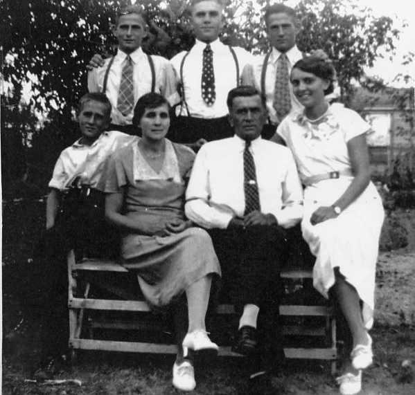 The W. L. Schwandt Family  Year: 1938  Place Name: Strasburg  Seated on the bench l. to r. are Son Harold (Hal), Mother Louise, Father W. L., and Daughter Hertha.  Standing l. to r. Theodore (Ted), Arthur (Art), and Frederick (Fred).