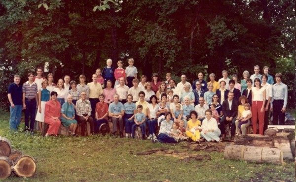 Shepherd family reunion - 1980. Year: 1980 Place Name: Glenwood, Minnesota Image Source: commercial photographer Photograph of the first Shepherd family reunion, held in 1980 in Glenwood, Minnesota, at the summer home of Fritz and Joy Munn. Of the senior generation (children of Grandfather and Grandmother), Eleanor and Geoff are seated in front on the left, to the right of Joy in red. Helen in about 1/3 of the way in from the right, in the blue reunion T-shirt, with white hair, and in front of the seated lady in yellow. The banquet the evening before was almost devastated with a near-hurricane, blowing down many trees. The fallen trees were used for seating, and are evident in the foreground as well.